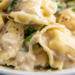 Up close image of cheesy baked tortellini on a plate with spinach.