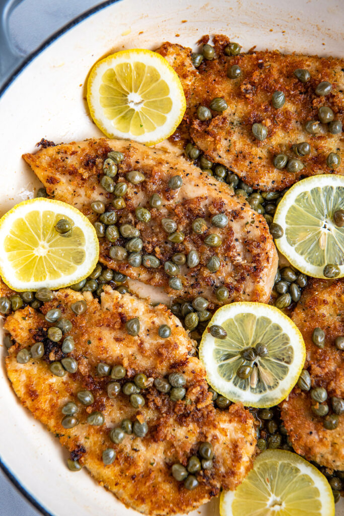 Chicken piccata in a white cooking pan with lemon slices