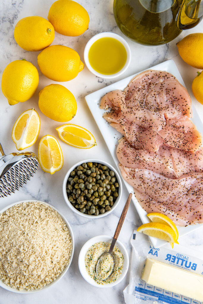 Lemons, capers, breadcrumbs, garlic salt and raw chicken breast on a plate