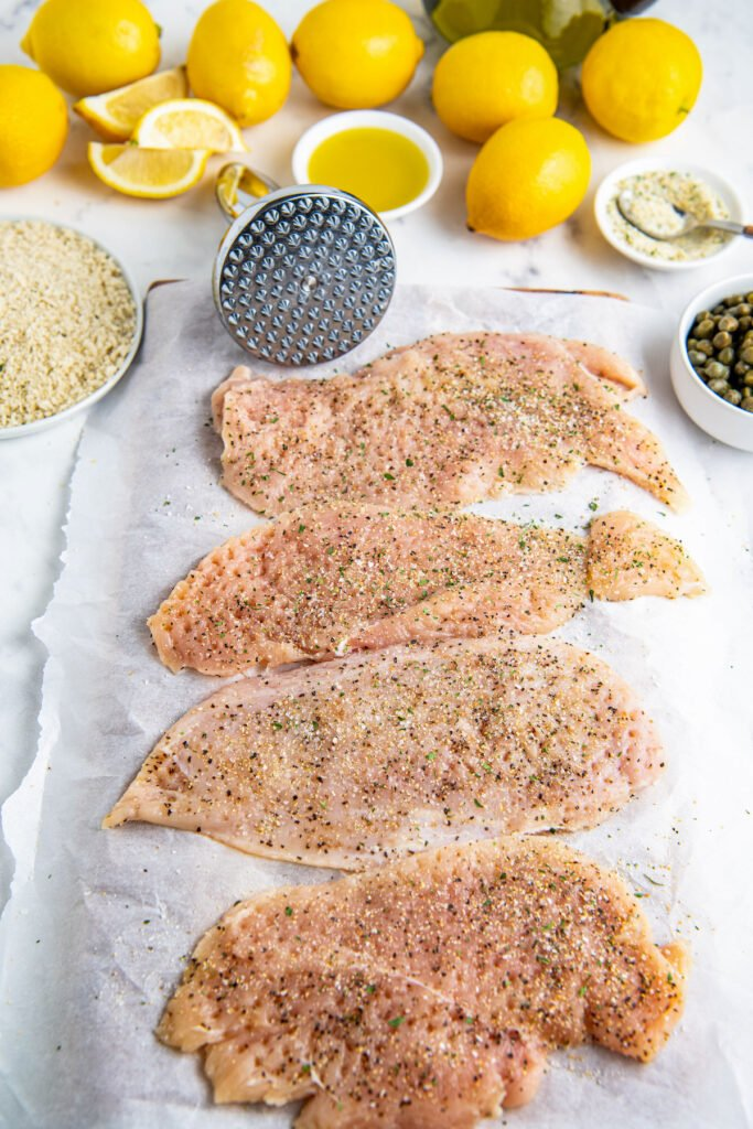 Raw chicken breast with seasoning and lemons and capers