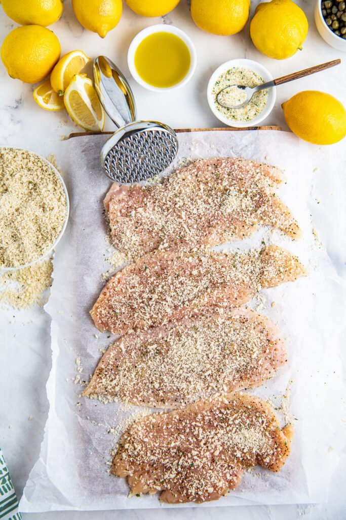 Raw chicken breast with breadcrumbs and lemons, olive oil and seasonings