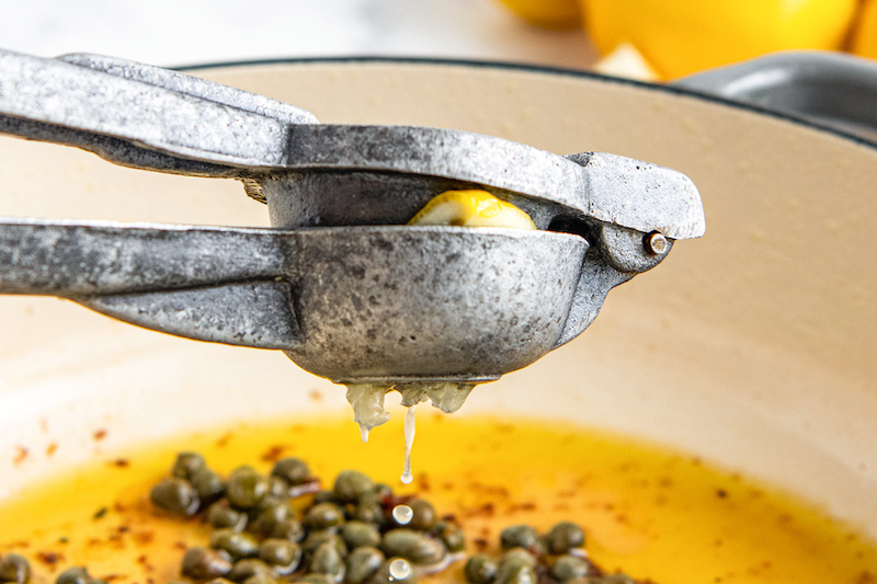 Lemon squeezed into pan with capers and oil