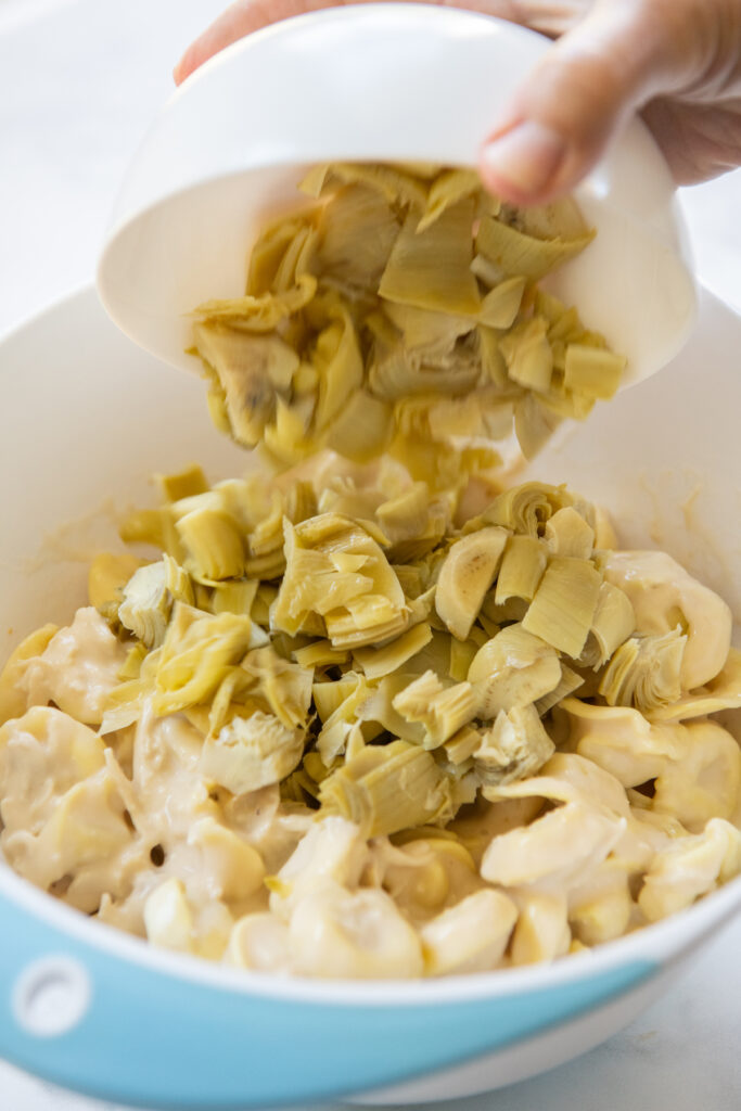 Artichokes poured into a mixing bowl with tortellini.