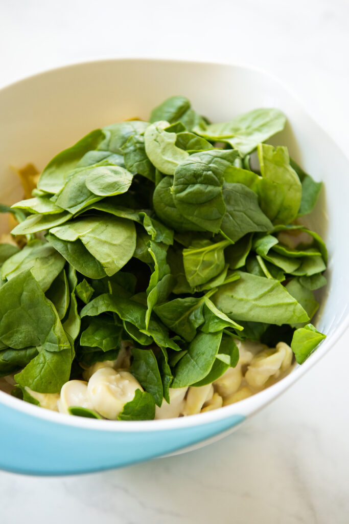 Fresh spinach added to a mixing bowl of tortellini.