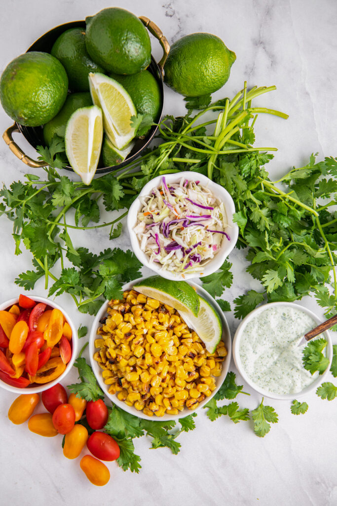 Toppings for avocado tacos lime slices, roasted corn, cherry tomatoes, cilantro, shredded cabbage and crema lime cilantro