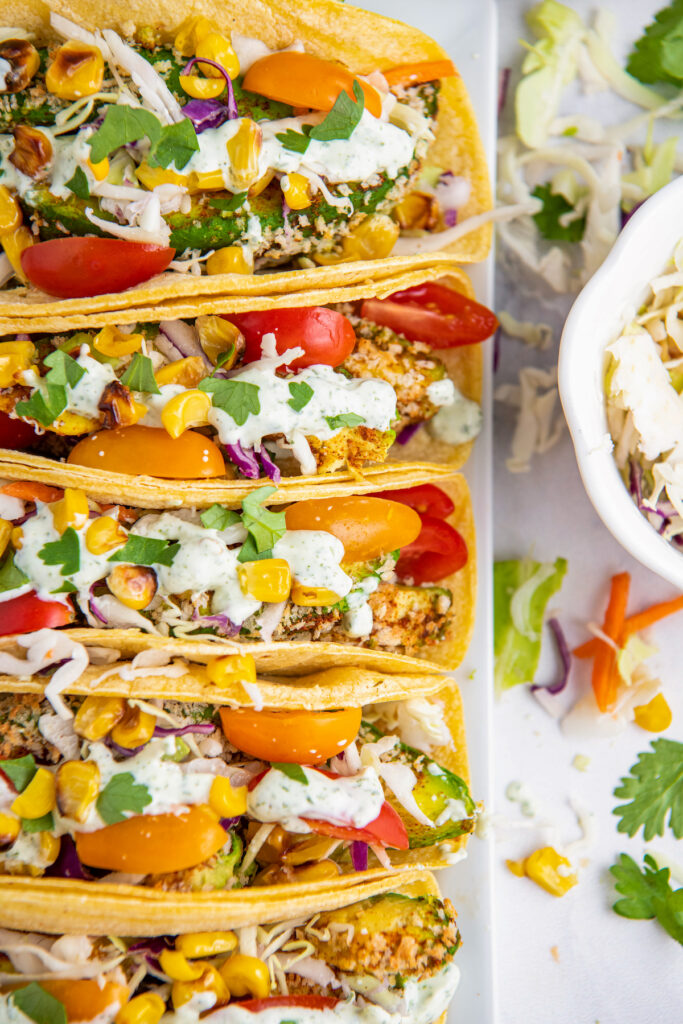 Tacos on white plate stuffed with avocados, corn, tomatoes, sliced cabbage and crema