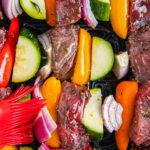 Shish kabobs in an air fryer with a basting brush.
