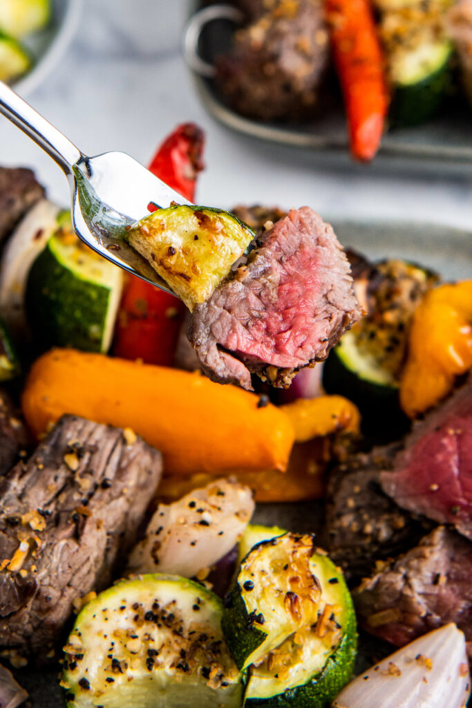A for with steak and zucchini above a plate with steak, peppers, zucchini and onions.