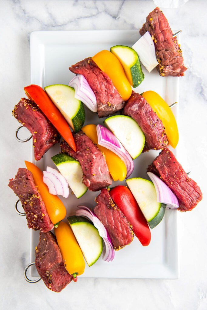 3 shish kabobs on a white plate