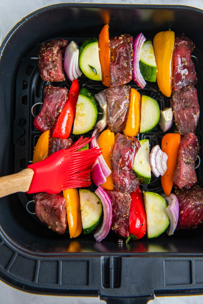 Shish kabobs in an air fryer with a basting brush