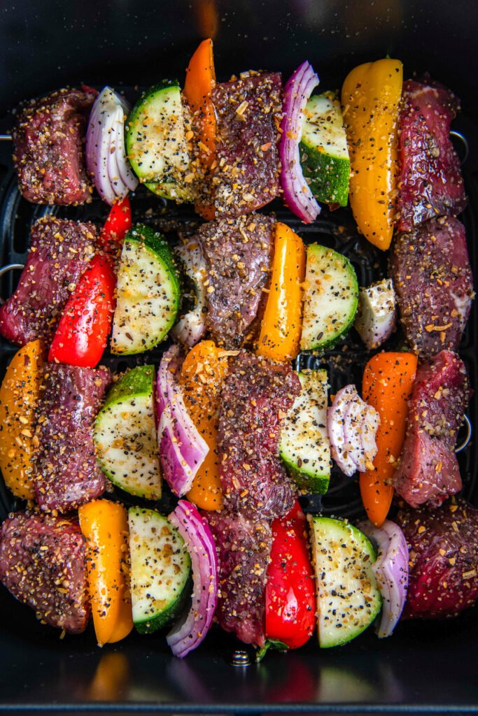 Raw shish kabobs with meat, zucchini, onions and peppers in an air fryer