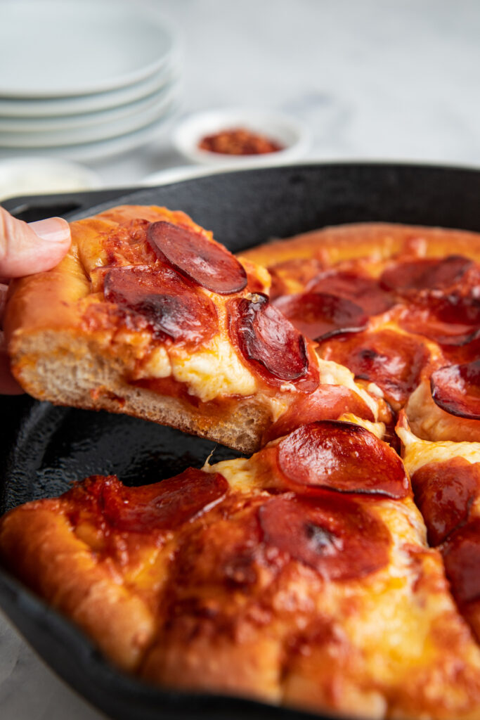 Sliced pepperoni pizza in a cast iron skillet