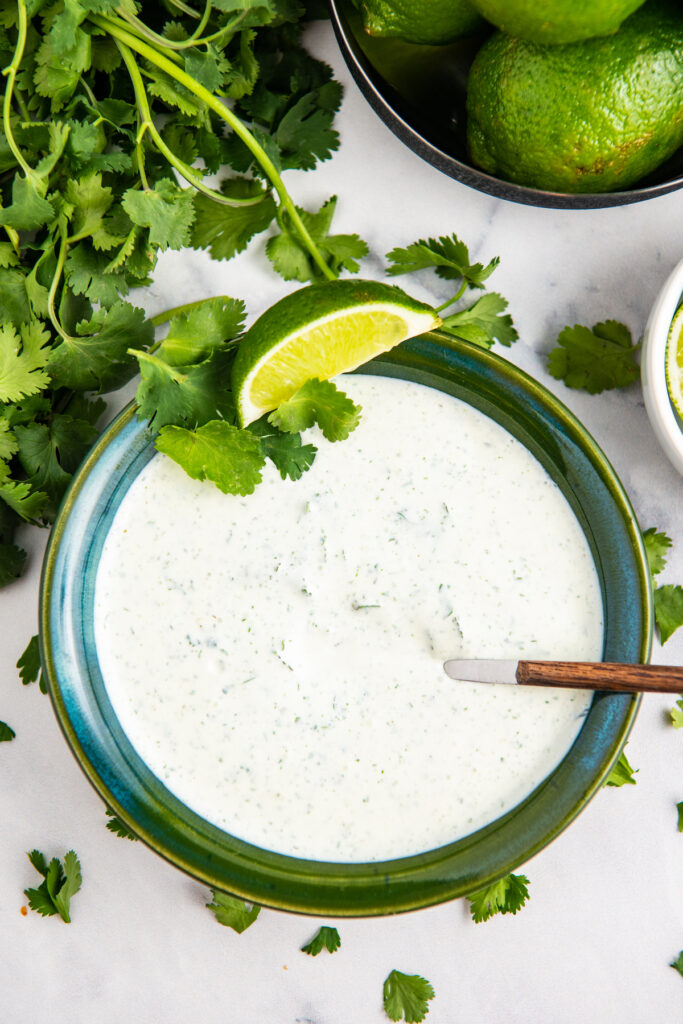 Cilantro Lime Crema in a green bowl with lime wedges and fresh cilantro