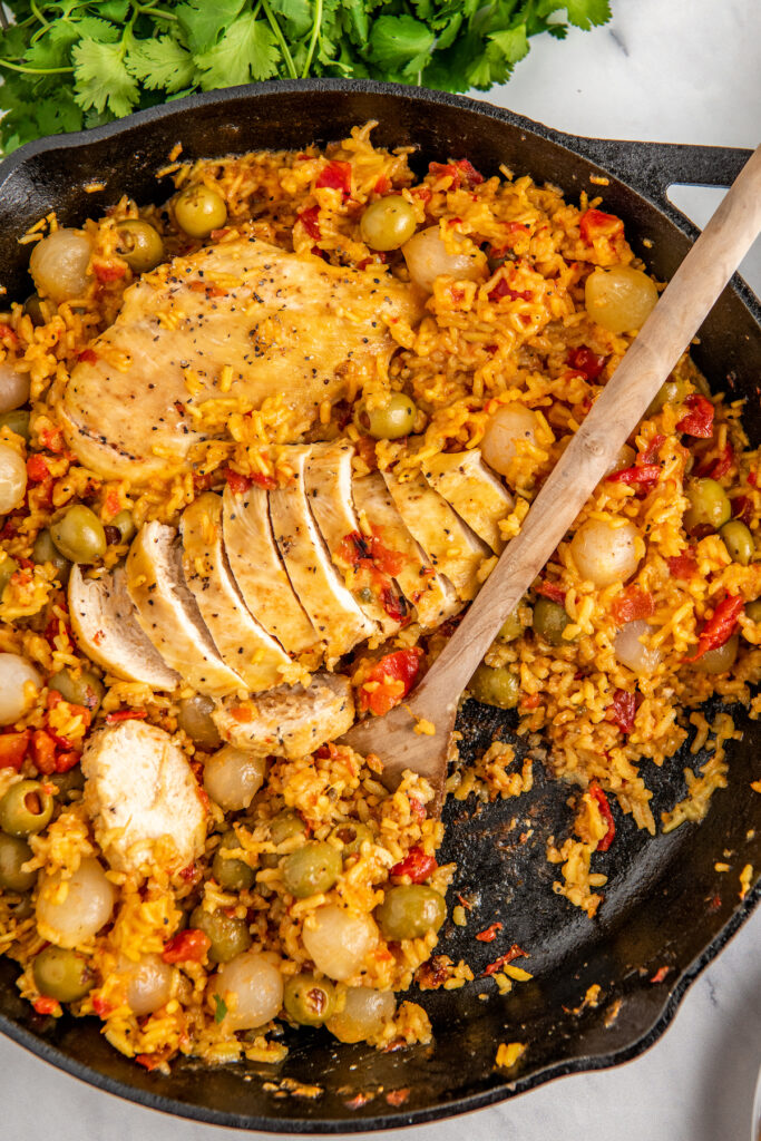 Cast iron skillet with Spanish chicken and rice and a wooden serving spoon