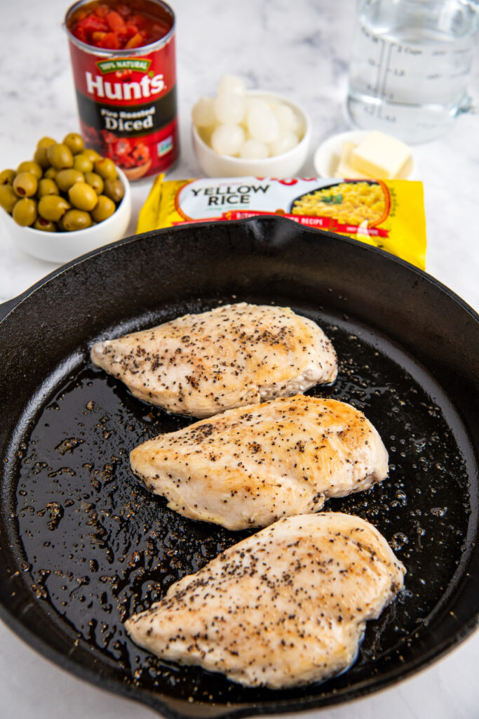 Cast iron skillet with seared chicken breast along with olives and onions in white bowls a bag of rice and a can of tomatoes