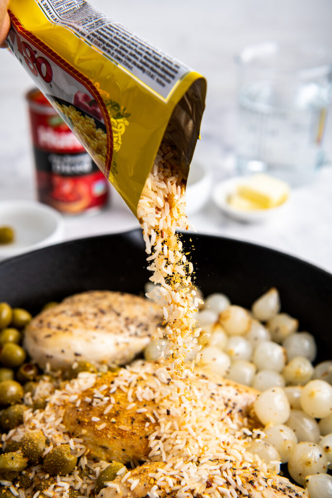 Rice being poured into a cast iron skillet with chicken breast, olives and cocktail onions