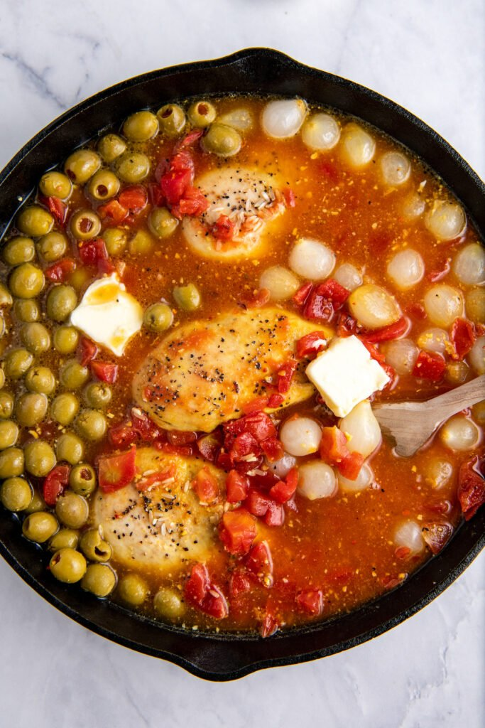 Cast iron skillet with chicken, olives, onions, tomatoes and butter