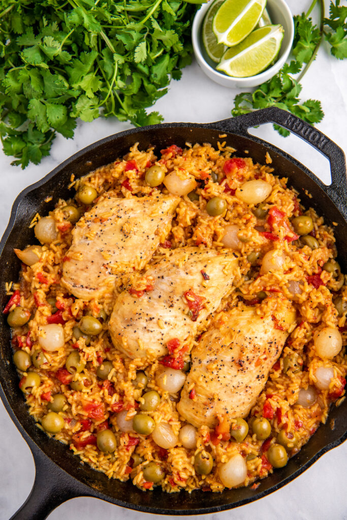 Cast iron skillet with Spanish rice and chicken. the rice has olives and onions in it and parsley on the side