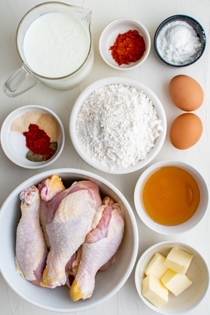 The ingredients for this chicken recipe are placed on a white surface.