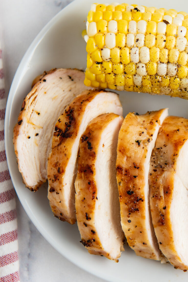 Cut grilled chicken on a white plate with corn on the cob