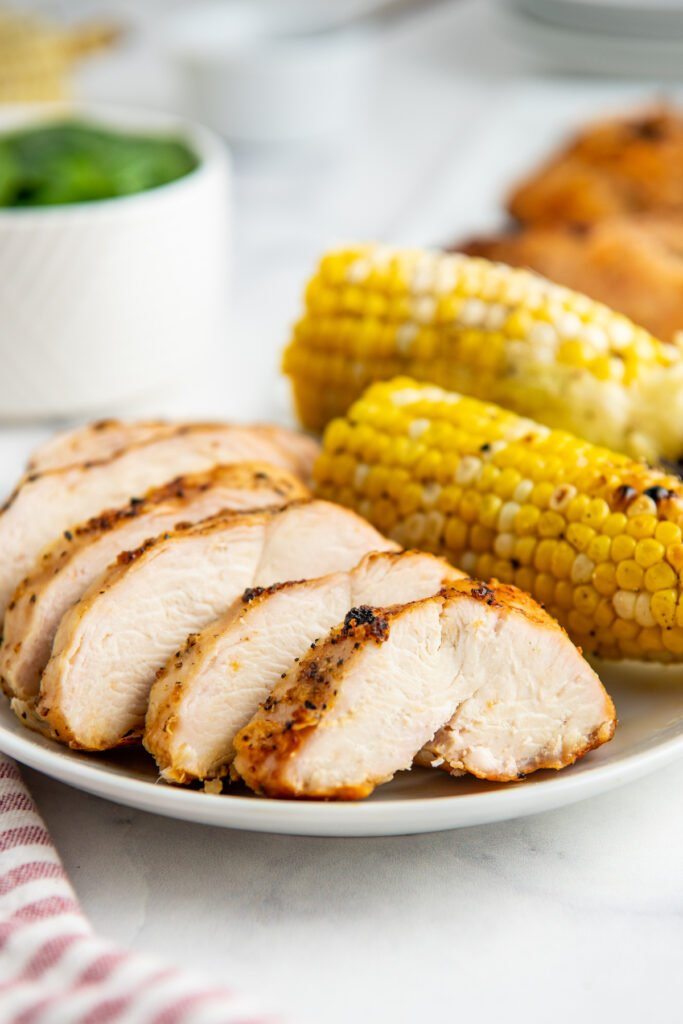 Grilled chicken breast with grilled yellow corn on a white plate