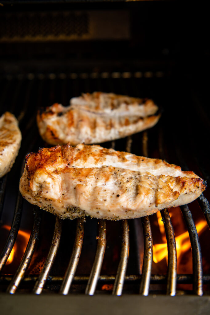 Chicken breast on a gas grill with flames under them