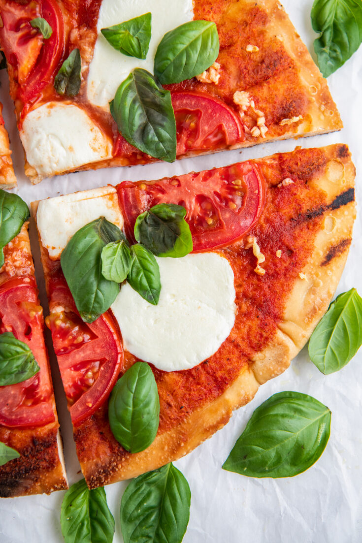 A slice of grilled margherita pizza with fresh basil
