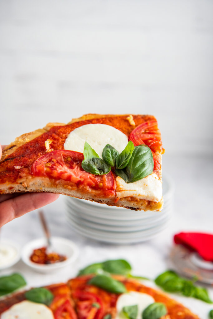 A piece of grilled Margherita pizza held over more pizza