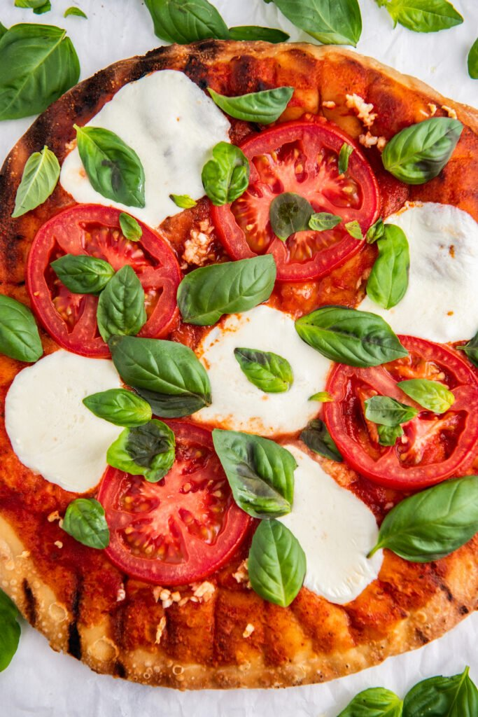 A margherita pizza with fresh mozzarella, sliced tomatoes and basil