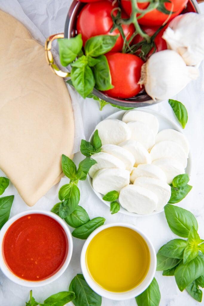 Pizza dough, fresh basil, olive oil, tomato, mozzarella cheese and pizza sauce