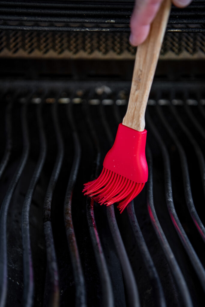 Gas grill with a red basting brush applying olive oil to the grate