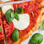 Up close image of grilled pizza with basil and mozzarella on top.