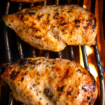 3 Large chicken breast on a gas grill cooking.