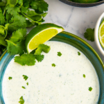 Cilantro cream sauce in a green bowl with lime wedges and fresh cilantro