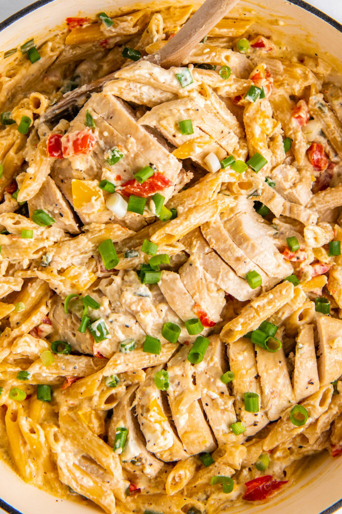 A sliced chicken breast is in a pot with creamy cajun pasta.