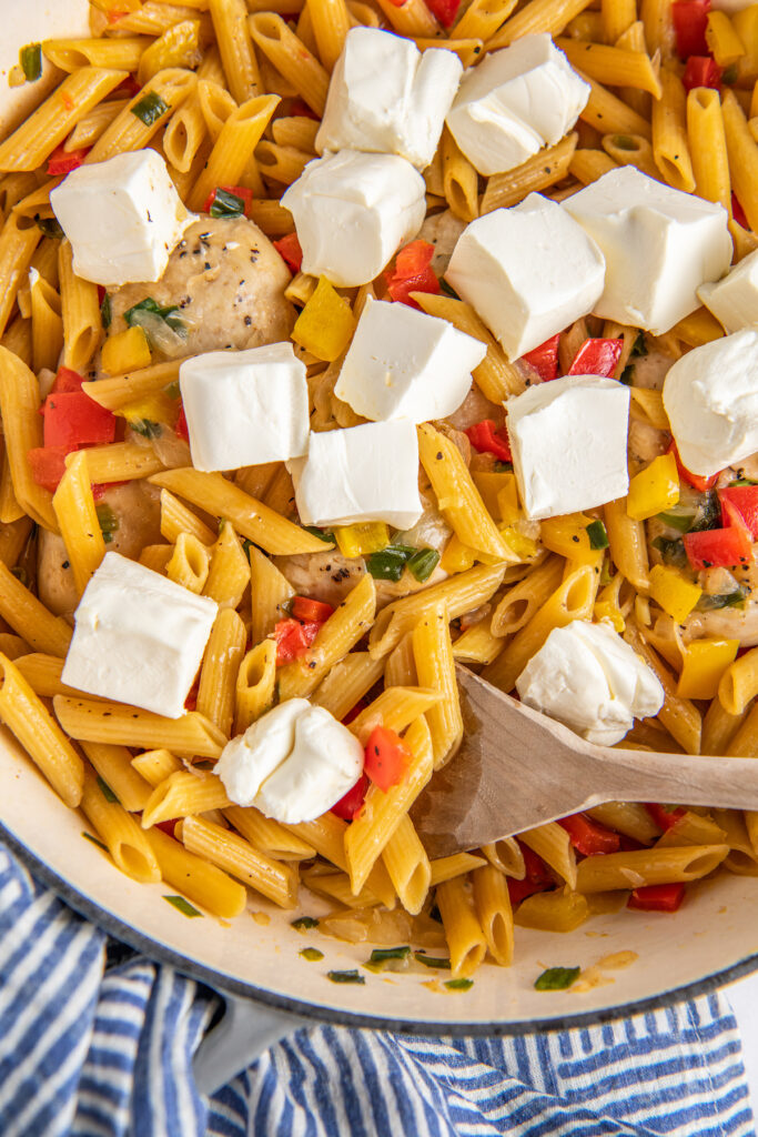 Chunks of cream cheese are in a pot with pasta and veggies.