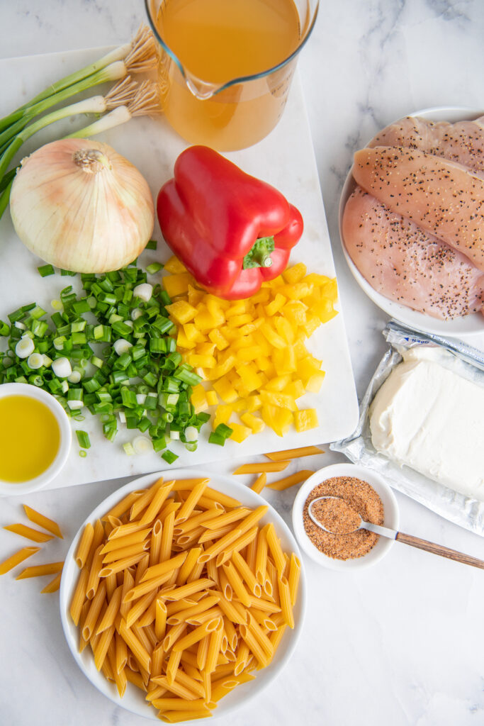 The ingredients for Cajun Chicken Pasta are placed on a white surface.