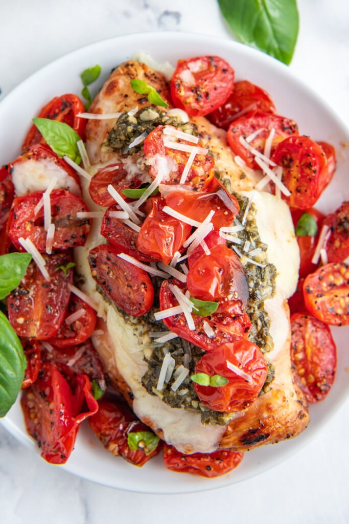 Tomatoes and grilled chicken are topped with shredded cheese.