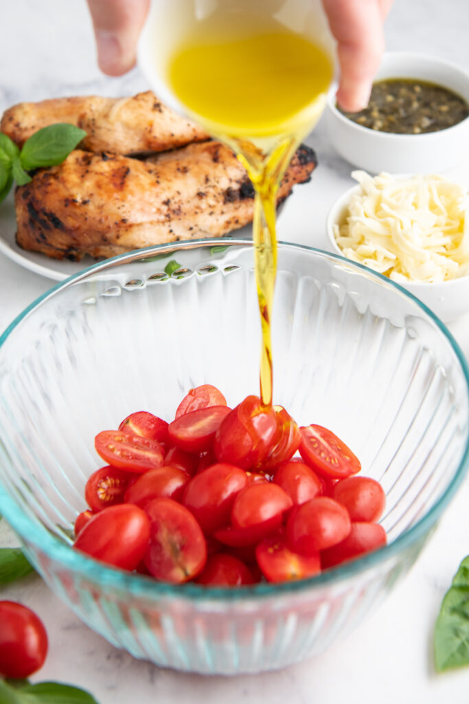 Olive oil is being poured over tomatoes in a glass bowl.