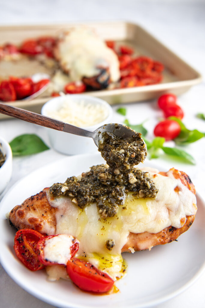 Pesto is being placed on top of a prepared cheesy chicken breast.