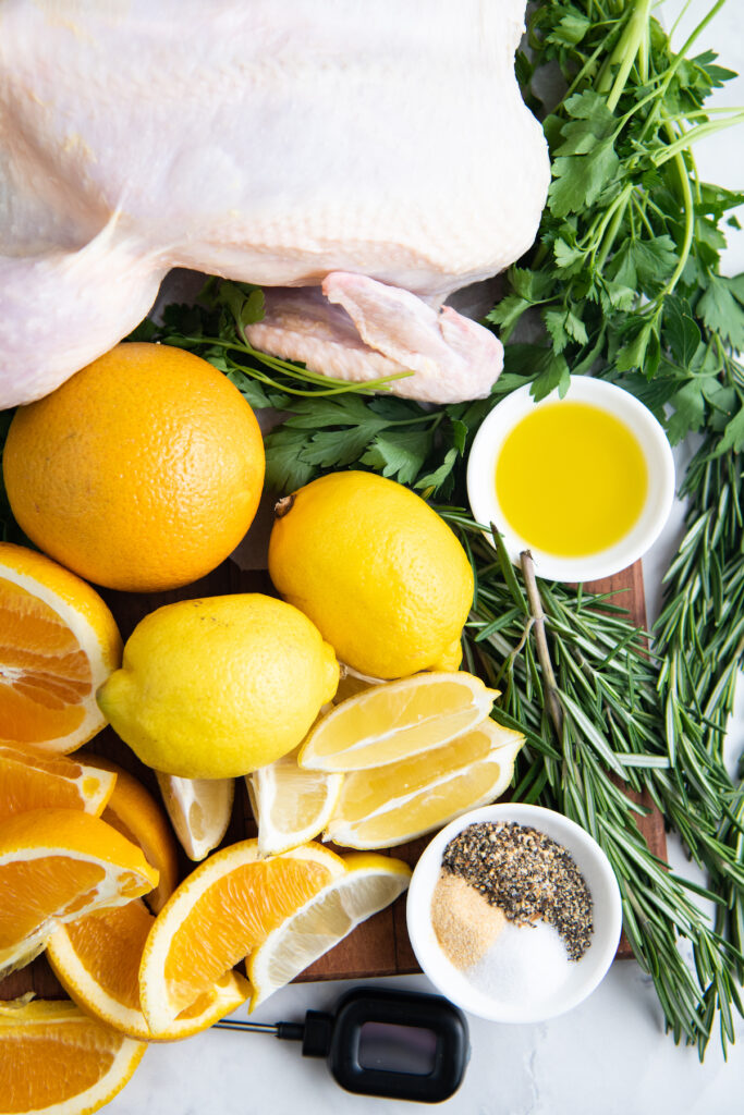 The ingredients for roasted chicken are placed on a white surface.