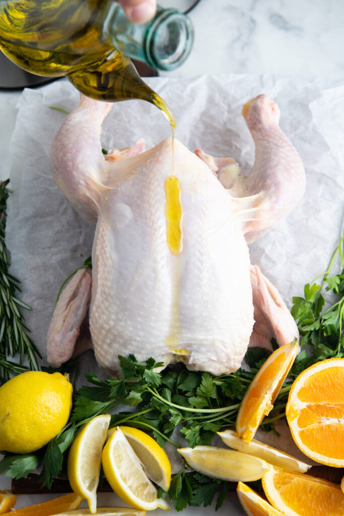 An uncooked whole chicken is drizzled with olive oil.
