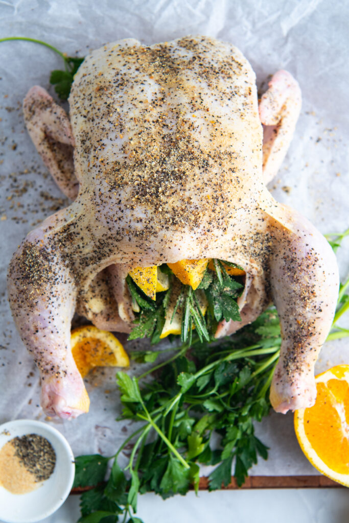 A seasoned chicken is stuffed with herbs and citrus.
