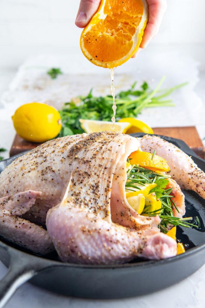 Orange juice is being squeezed on top of the seasoned chicken.