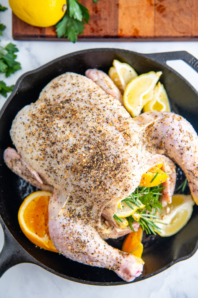 The prepared chicken is placed in a large black skillet with citrus wedges.