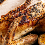 Up close image of roasted chicken being sliced into pieces.
