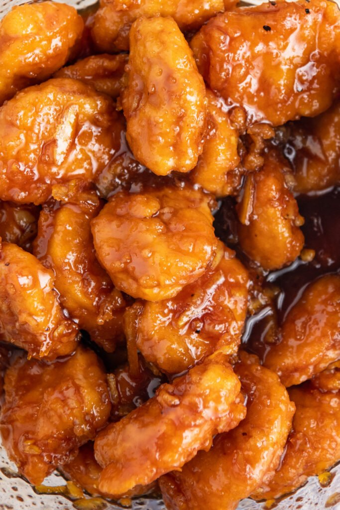 Up close image of chicken nuggets tossed in an orange sauce.