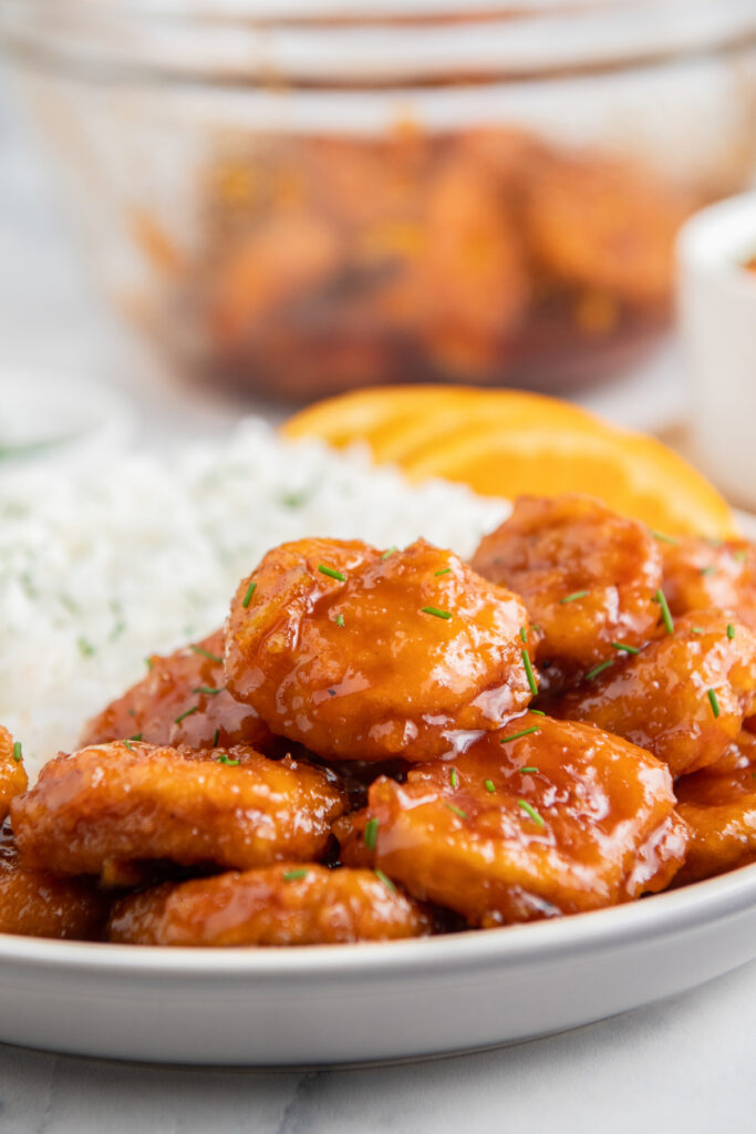 Air fryer orange chicken on a white plate with rice behind it.