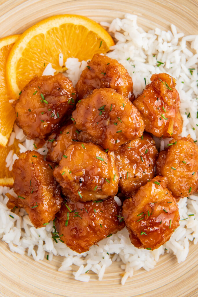 Air fryer chicken on a bed of rice with an orange slice in a brown bowl.