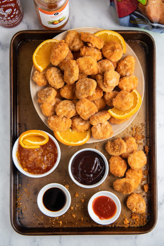 Chicken nuggets in a bowl with a sheet pan under holding the sauces in bowls.